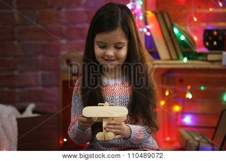 Pretty little girl playing with wooden plane in Christmas decorated room