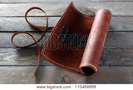 Leather case on wooden background