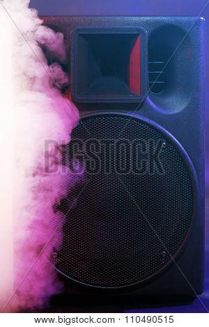 Black loudspeaker in a smoke on dark background