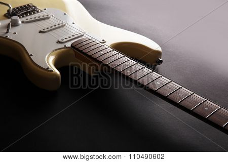 Part of white electric guitar, on black background