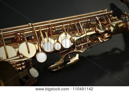 Beautiful golden saxophone on black background, close up