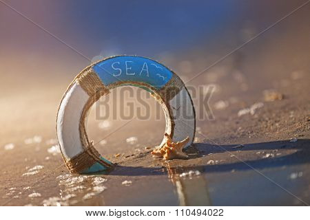 Beautiful life buoy in the sand with starfish on unfocused sea background
