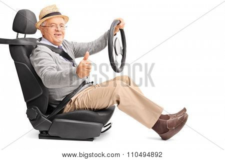 Senior gentleman pretending to drive seated on a car seat and giving a thumb up isolated on white background