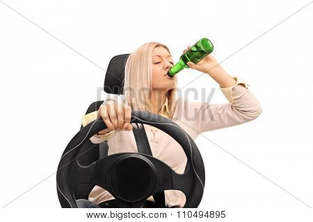 Studio shot of an irresponsible young woman drinking a beer and driving isolated on white background