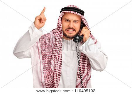 Studio shot of an angry Arab talking on telephone and threatening with his finger isolated on white background