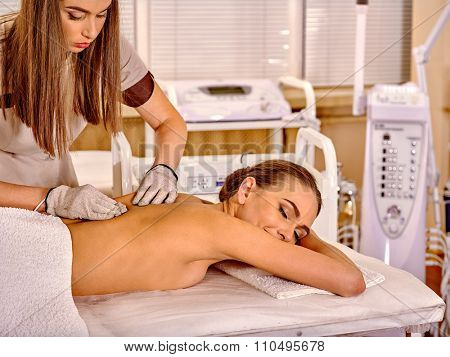 Young smiling woman  receiving electric massage at  hardware cosmetology beauty salon. Beautician wearing electricity gloves.