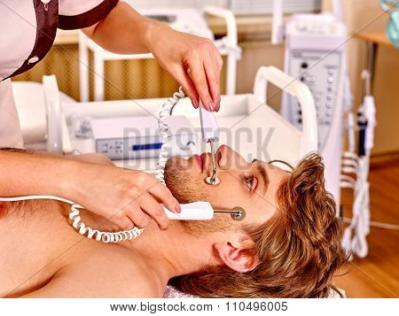 Close up of  man face receiving electric facial eyes massage on microdermabrasion equipment at beauty salon.
