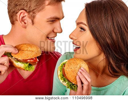 Young couple man and woman eating hamburgers and looking each other. Fastfood concept.  Isolated.