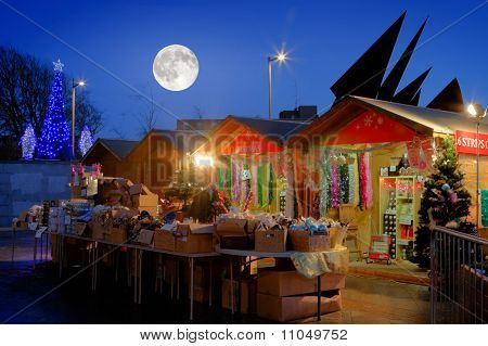 Christmas Market With Full Moon And Illuminated Tree At Night
