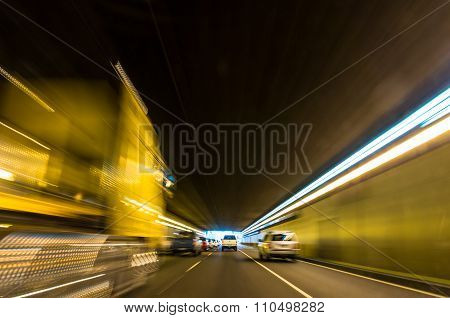 Blurry speeding car in a tunnel with light trails