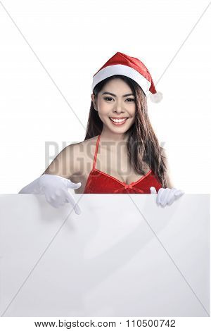 Young Attractive Asian Woman Wearing Santa Claus Costume Holding Blank Billboard