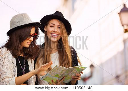 Two young women with city map as tourists