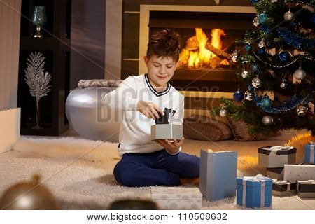 Satisfied little boy opening christmas box with mobilephone, sitting on floor, smiling.