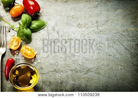 Fresh organic vegetables on rustic background (tomatoes, basil, garlic, olive oil). Healthy food. Vegetarian eating. Fresh harvest from the garden.