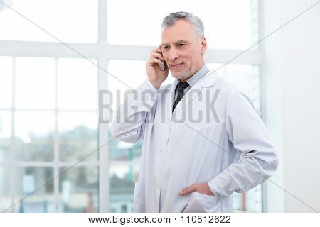 Aged doctor in hospital office