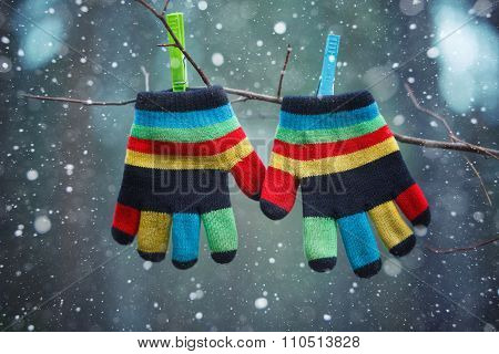 Little Baby Mittens/gloves Hanging By A Thread In Winter Day Under The Falling Snow.