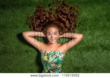 Portrait of pretty smiling young woman, laying on the grass