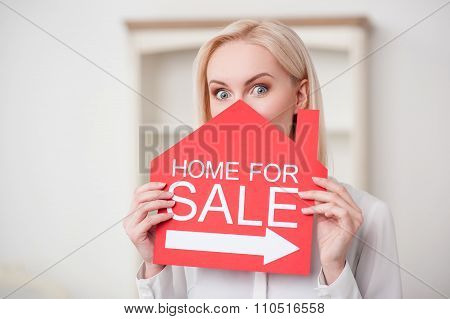 Attractive female realtor is selling a house