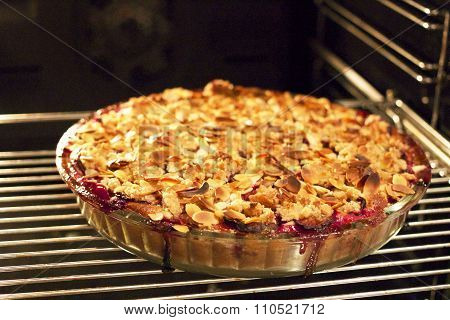Freshly Baked Plum Pie With Almonds And Crumble On Top In The Oven