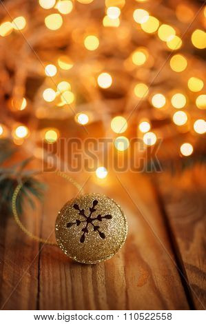 Gold Metal Jingle Bell With Snowflake On Wooden Table With Boke.