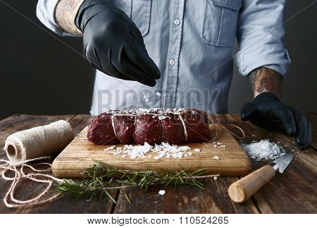 Tattoed Butcher In Black Gloves Salts Tied Piece Of Meat To Smoke It.