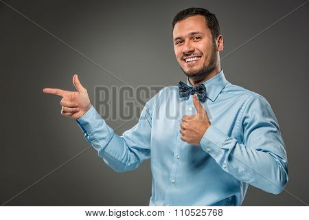 Smiling man pointing to something with an index finger