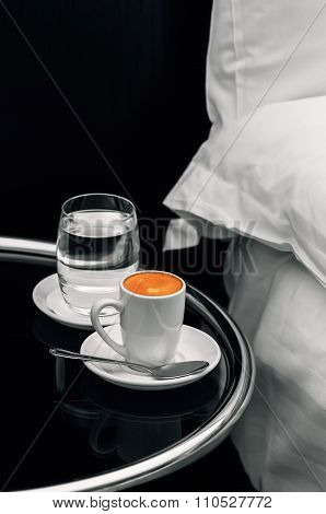 Espresso coffee full cup and glass of water on bedside table closeup