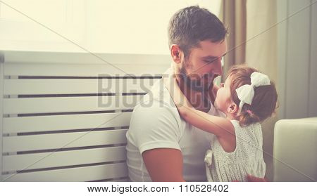 Happy Family Child Baby Girl In Arms Of His Father At Home