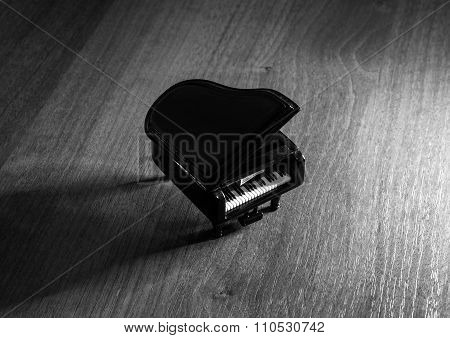 Miniature Model Of Black Grand Piano With Shadow On Wooden Table Black And White