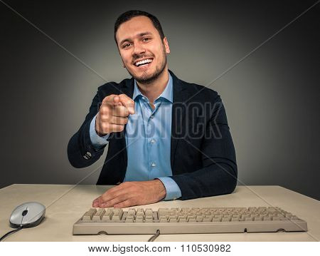 Smiling man is gesturing with hand, pointing finger at camera