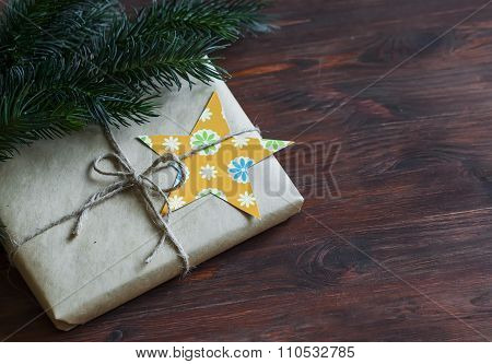 Homemade Christmas Gifts In Kraft Paper With Handmade Tags And A Christmas Tree On Dark Brown Wooden