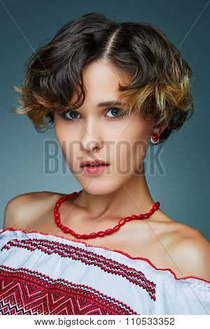 Portrait charming young lady with short wavy hair in embroidery.