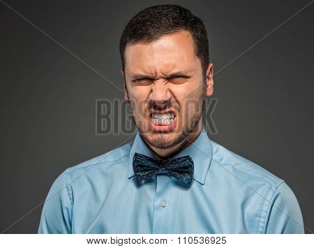 Portrait angry upset young man in blue shirt, butterfly tie