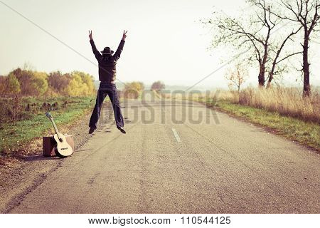 Backview of guitar player in hat jumping on countryside road