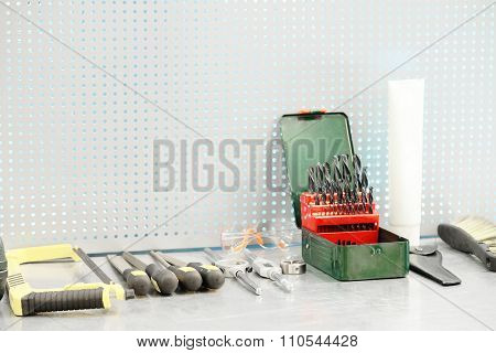 Various size drill bits in iron box on the working place