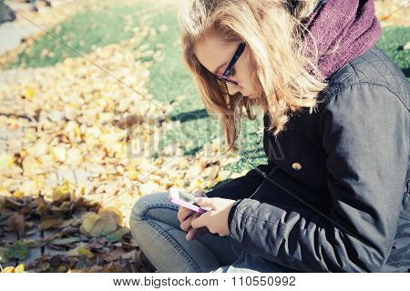 Bllond Teenage Girl In Glasses Sitting In Autumnal Park