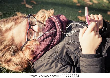 Caucasian Blond Teenage Girl Laying In Autumnal Park