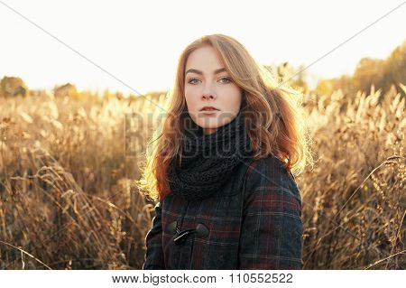 Noon portrait of young beautiful redhead woman in scarf and plaid jacket standing on faded meadow co