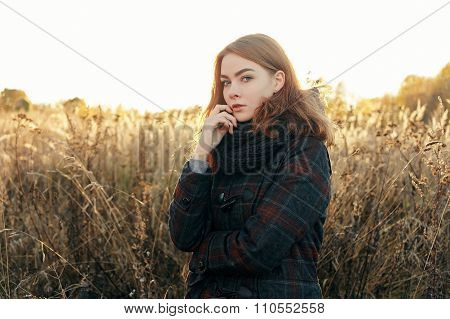 Noon portrait of young thoughtful redhead woman in scarf and plaid jacket standing on faded meadow c