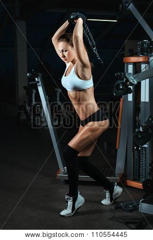 Woman Lifting Weights On A Machine For Bodybuilders.