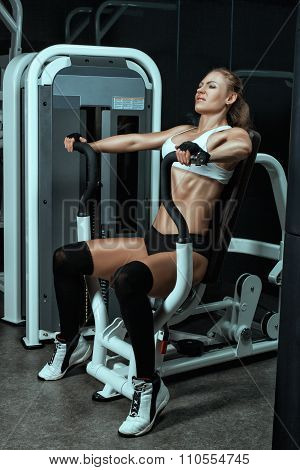 Girl Shakes Her Arm Muscles On The Machine For Bodybuilders.