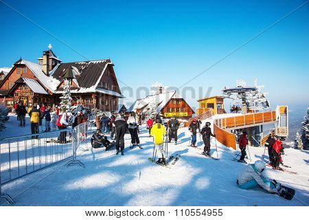 KOHUTKA, CZECH REPUBLIC - JANUARY 16, 2010: Ski resort in the Czech Tatra. Houses with peaked roofs. Frosty sunny winter day. Skiers in bright jackets are preparing to descend on skis
