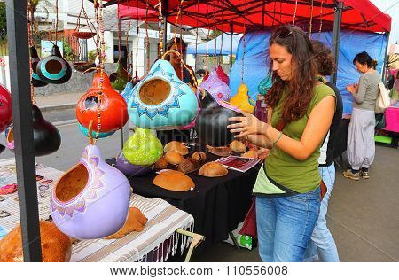 SAINT-PIERRE, REUNION ISLAND, FRANCE - NOVEMBER 8, 2015: Unidentified woman shoppping on local farmers market. Traditional hand made products from calabash. African art.