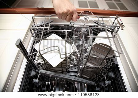 Woman's Hand Opening Dishwasher With Clean Utensils