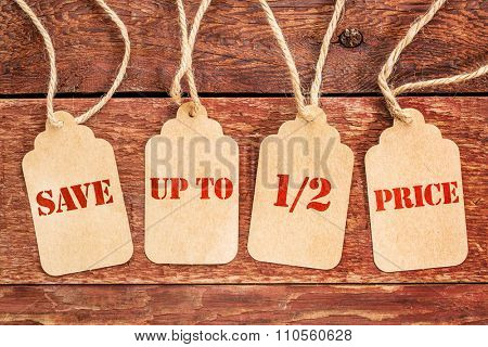save up to half price banner  - sign on paper price tags against a rustic barn wood