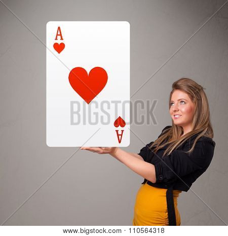 Beautifu young woman holding a red heart ace
