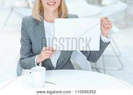Positive businesswoman holding sheet of paper
