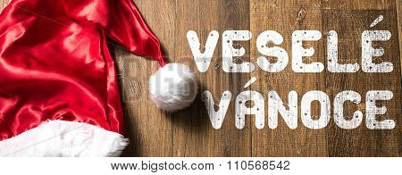 Merry Christmas (in Bohemian) written on wooden with Santa Hat