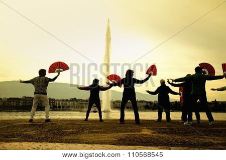 Silhouette of people doing tai chi in a park and fountain in background
