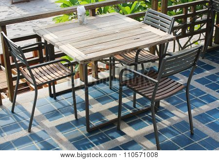 Wooden table with blue tiles in the outdoor coffee room.